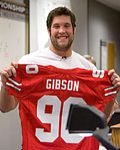 Scarlet Captain Alex Boone holds up the jersey of number one overall pick Thaddeus Gibson