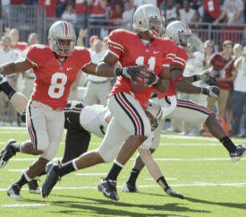 After picking up a blocked punt by teammate Malcolm Jenkins, far right, Ohio State's Etienne Sabino (11) runs the ball in for a touchdown against Purdue in first quarter NCAA college football action in Columbus, Ohio on Saturday, Oct. 11, 2008. Trailing Sabino is OSU's Aaron Gant (8) and Purdue's Joe Holland. (AP Photo/Amy Sancetta)